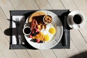white plate on a black table mat with brunch items including sunny side up eggs, bacon, potato pieces, pancakes with syrup, and a fruit medley next to a cup of coffee