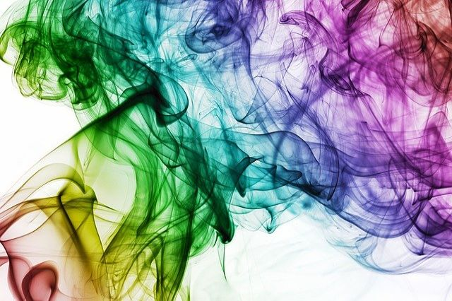 a smoke of rainbow colors in front of a white background